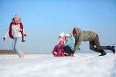 Riding on sledge. Happy kids enjoying riding on sledge with their parents Stock Image