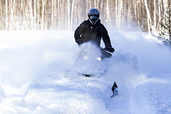 Riding snowmobile covered in snow Stock Photo