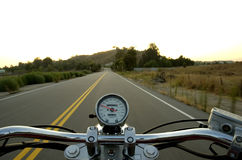 Riding a straight road. Motorcycle moving on a straight road from rider's perspective Stock Image