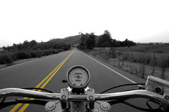 Riding a straight road. Motorcycle moving on a straight road from rider's perspective Royalty Free Stock Photography