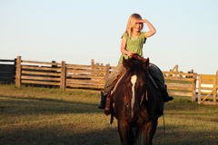 Riding into the Sunset. A beautiful young blonde girl horseback shading her eyes with her hand Royalty Free Stock Photos