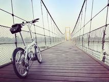 Riding through suspension bridge. Morning exercise with my bicycle Stock Image