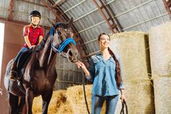 Dark-haired stylish riding teacher leading horse with cute girl royalty free stock photography