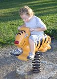 Riding Tiger. Young boy riding playground tiger ride while outdoors Royalty Free Stock Photos