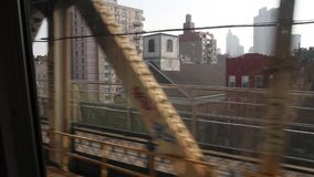 Riding a train Brooklyn to Manhattan in New York. Train crossing bridge in New York with the noise of the tracks and New York skyline and Brooklyn Bridge in the stock video footage