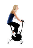 Riding training bike. Young blonde woman training on exercise bike in gym Stock Photos