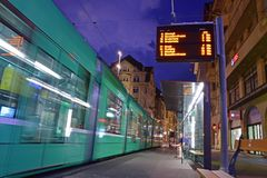 Riding the tram in Basel with moving green tram on the left & Marktplatz station on the right during night time Royalty Free Stock Image