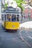 Riding tram in narrow, curvy street, Lisbon Stock Image