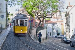 Riding tram in narrow, curvy street, Lisbon Stock Photo