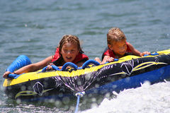 Riding the Tube. Two children enjoying a fun ride on the lake Stock Images
