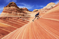 Riding The Wave. A hiker scales the petrified sandstone formations at The Wave in the Coyote Buttes section of the Paria Canyon-Vermilion Cliffs Wilderness in Royalty Free Stock Photos