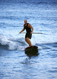 Riding a Wave. Tom Thayer taking a break and surfing with an oar royalty free stock photos