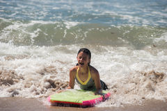 Riding the wave all the way in. Girl child landing on the sand as she rides the boogie board Stock Photo