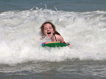 Riding the Waves. A young girl having a great time boogie boarding at the beach Stock Photos