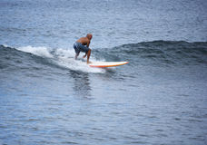 Riding the Waves. Older gentleman riding waves in the pacific ocean stock photos