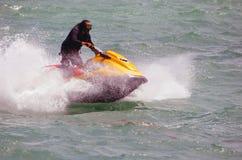 Riding Waves on a Yellow Jet Ski Stock Photos