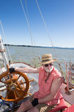 Riding the Wind. A senior man at the helm of sailboat navigates on Fern Ridge Reservoir near Eugene, Oregon stock photo