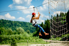 Riding on a zip line. Young woman in casual wearing with red helmet riding on a zip line in the mountains. Active kind of recreation stock photo