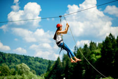 Riding on a zip line. Young woman in casual wearing with red helmet riding on a zip line in the mountains. Active kind of recreation stock photography