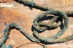 Ridit ut nautiskt rep på en pir Arkivbild