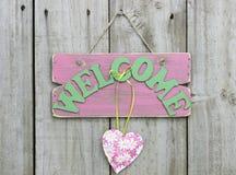 Ridit ut rosa välkommet tecken med blommahjärta som hänger på trädörr Royaltyfria Foton