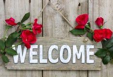 Ridit ut välkommet tecken med röda blommor som hänger på gammal wood dörr Royaltyfri Fotografi