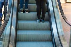 Ridning för flickaklädergymnastiksko på en rulltrappa fot som står på rulltrappan Royaltyfri Bild