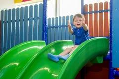 Ridning för liten unge från barns glidbanor i tummar för modig mitt och showupp Lycklig liten unge, barn som upp rider, ner på gl arkivfoton