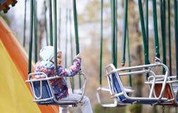 Ridning för litet barn på en chaing gunga royaltyfri fotografi