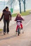 ridning för moder för cykelbycicleflicka liten Royaltyfria Bilder