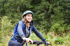 Ridningcykel för ung kvinna i bergskog Royaltyfria Bilder