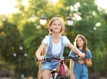 Ridningcykeln för den tonårs- flickan med vänner parkerar in royaltyfria bilder