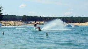 Ridningen Wakeboard för den unga mannen på sjön parkerar Flytta sig in i kamera och krasch in i vatten stock video