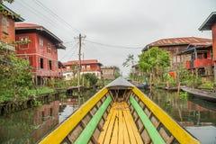 Ridningfartyg bland att sväva byn på Inle sjön POV i den Myanmar Burman Royaltyfri Foto