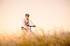 Ridningmountainbiken för ung kvinna i det härliga fältet av fjädergräs på solnedgången Affärsföretag och lopp fotografering för bildbyråer
