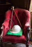 Ridningsilke och hatt på röd sammetstol Fotografering för Bildbyråer