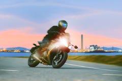 Ridningsport för ung man som turnerar motorcykeln på asfalthuvudvägar ag Arkivbilder