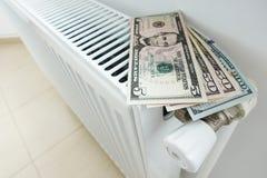 Riduca la vostra fattura di energia per il riscaldamento della casa con le banconote dei dollari americani sul radiatore bianco fotografie stock libere da diritti