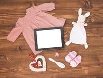 Riduca in pani i vestiti dei bambini e del computer su fondo di legno Fotografia Stock