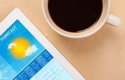 Riduca in pani il pc che mostra le previsioni del tempo sullo schermo con una tazza di coffe Fotografia Stock