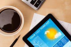 Riduca in pani il pc che mostra le previsioni del tempo sullo schermo con una tazza di coffe Immagini Stock Libere da Diritti