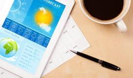 Riduca in pani il pc che mostra le previsioni del tempo sullo schermo con una tazza di coffe Fotografie Stock Libere da Diritti