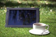 Riduca in pani il pc e una tazza di caffè sull'erba Immagine Stock