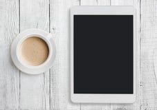 Riduca in pani il pc sullo scrittorio bianco della tavola con la tazza di caffè Immagine Stock