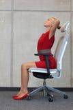 Riduzione di sforzo del lavoro d'ufficio - donna che si esercita sulla sedia Fotografia Stock