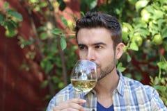 Riechen eines gutaussehenden Mannes und trinkender Wein Lizenzfreie Stockbilder