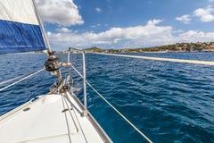 Riechen Sie Boot mit einem Segel auf dem Hintergrund des Ufers Lizenzfreie Stockfotos