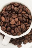 Kaffeebohnen in der weißen Schale und in der Platte stockfotografie
