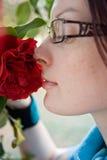 Riechende Blume der jungen Frau stockfoto