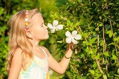 Riechende Blume des kleinen Mädchens Lizenzfreies Stockfoto